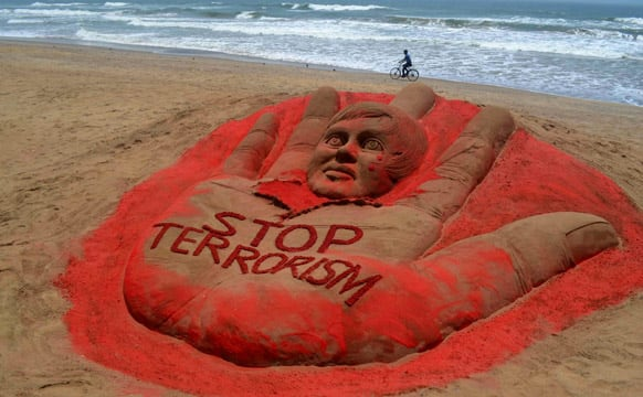 A cyclist pedals past a sculpture with a message against terrorism, created after attacks in Boston and Bangalore, at the golden sea beach in Puri.