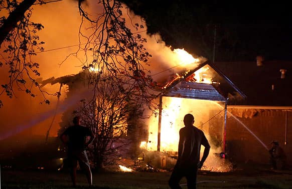 A person looks on as emergency workers fight a house fire after a near by fertiliser plant exploded in West, Texas.