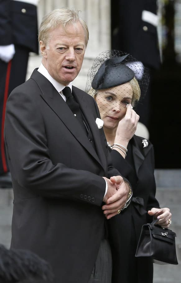 Mark Thatcher, looks on as his wife Sarah wipes her eyes after the coffin of his mother, former British Prime Minister Margaret Thatcher was carried by pallbearers out from St Paul`s Cathedral, following the ceremonial funeral service in London.