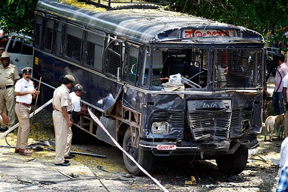Policemen secure the area around a damaged police bus after an explosion in a residential neighborhood near the office of India`s main opposition Bharatiya Janata Party, in Bangalore.