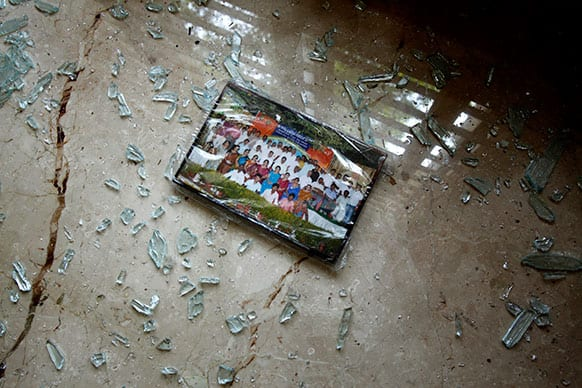 A photograph lies on the floor surrounded by broken glass inside a house after an explosion at a residential neighborhood near the office of India`s main opposition Bharatiya Janata Party, in Bangalore.