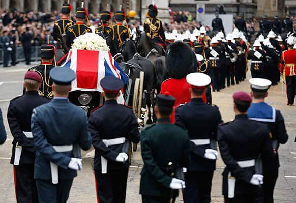 A Union flag draped coffin bearing the body of former British Prime Minister Margaret Thatcher is carried on a gun carriage drawn by the King`s Troop Royal Artillery during her ceremonial funeral procession in London.