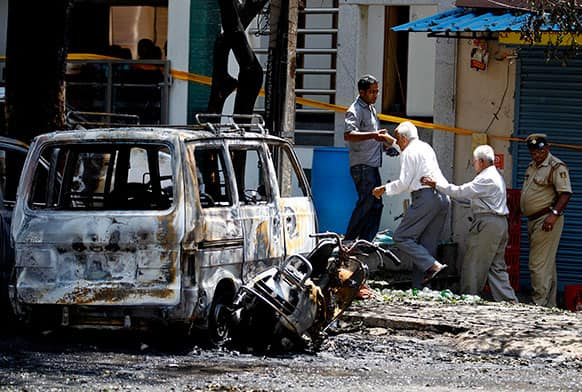 Elderly people walk past charred vehicles as they are taken to a safer place after an explosion in a residential neighborhood near the office of India`s main opposition Bharatiya Janata Party in Bangalore.