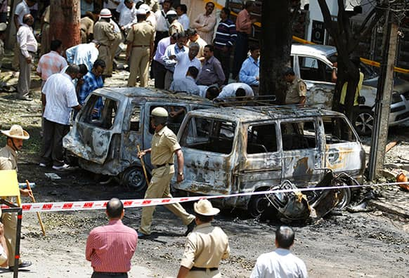 Policemen and officials inspect the site of an explosion at a residential neighborhood near the office of India`s main opposition Bharatiya Janata Party in Bangalore.