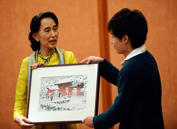 Myanmar opposition leader and Nobel Peace Prize laureate Aung San Suu Kyi receives a gift after her lecture at the University of Tokyo.