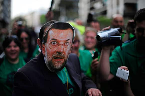 A man from Members of the Mortgage Victims` Platform (PAH) protests with a mask of Spain`s Prime Minister Mariano Rajoy against evictions in Barcelona.