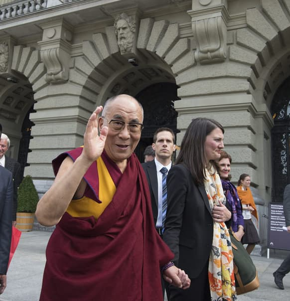 Tibetan spiritual leader Dalai Lama, waves to supporters next to Swiss National Council Tiana Angelina Moser during a visit in Bern, Switzerland.