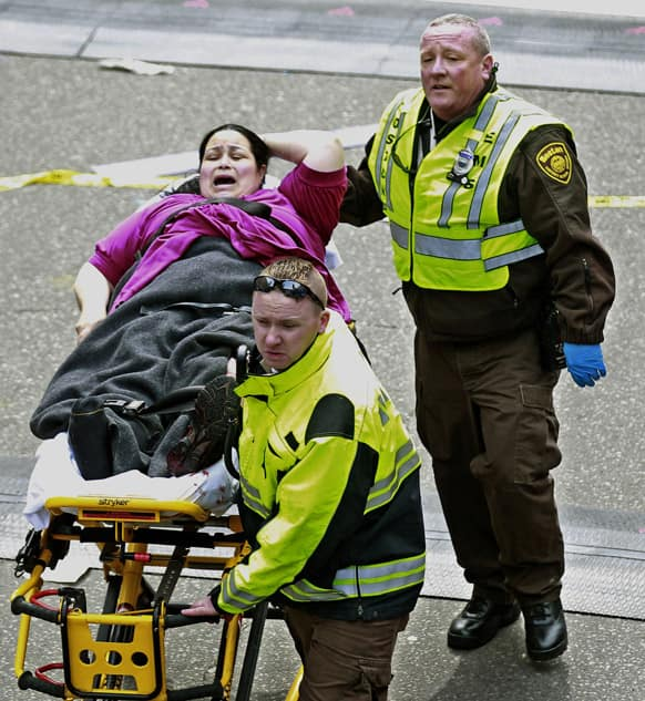 Medical workers aid an injured woman at the finish line of the 2013 Boston Marathon following two explosions there.