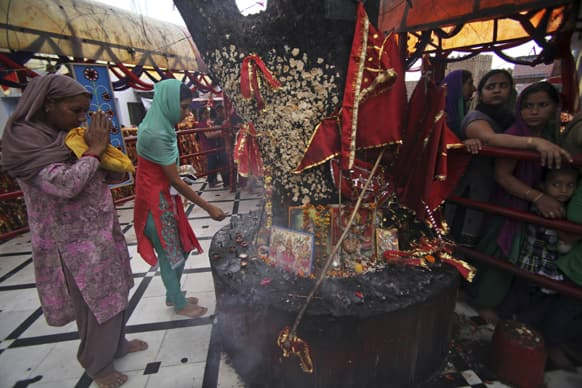Hindu devotees offer prayers as others stand in a queue inside the Kali Temple on during Navratri festival in Jammu. Navratri, or the festival of nine nights, is dedicated to the worship of various goddesses.