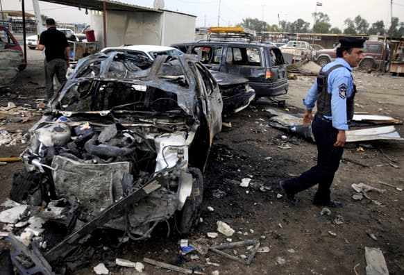 A policeman inspects the aftermath of a car bomb attack at a used cars dealers parking lot in Habibiya neighborhood of eastern Baghdad, Iraq.