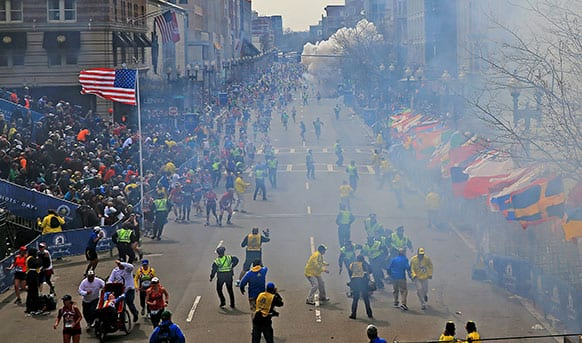 People react as an explosion goes off near the finish line of the 2013 Boston Marathon in Boston. Two explosions went off at the Boston Marathon finish line on Monday, sending authorities out on the course to carry off the injured while the stragglers were rerouted away from the smoking site of the blasts.