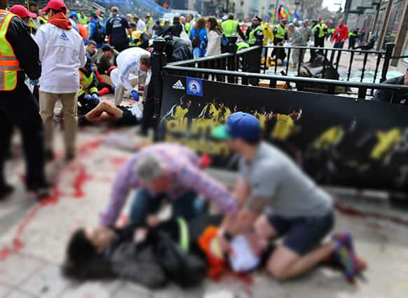 An injured woman is tended to at the finish line of the Boston Marathon, in Boston.