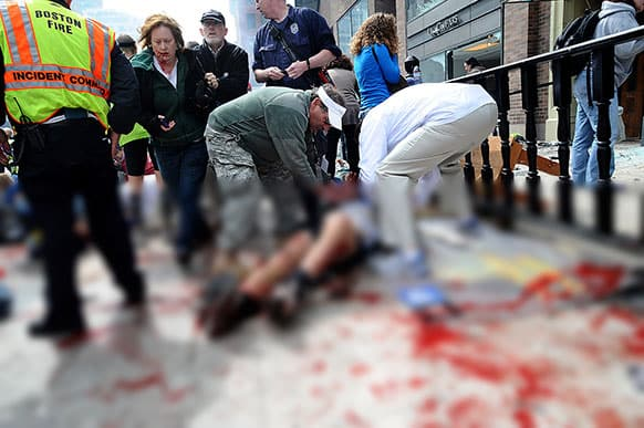 An injured person is helped on the sidewalk near the Boston Marathon finish line following an explosion in Boston.