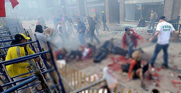 Injured people and debris lie on the sidewalk near the Boston Marathon finish line following an explosion in Boston.