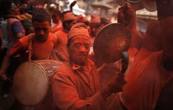 Nepalese devotees, covered in vermilion powder, beat drums and dance during Sindur Jatra festival in Thimi, on the outskirts of Katmandu.