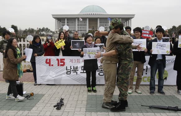 Anti-war activists wearing military clothes of a North, left, and South Korea hug each other during a rally to mark Global Day of Action on Military Spending in front of the National Assembly in Seoul, South Korea.