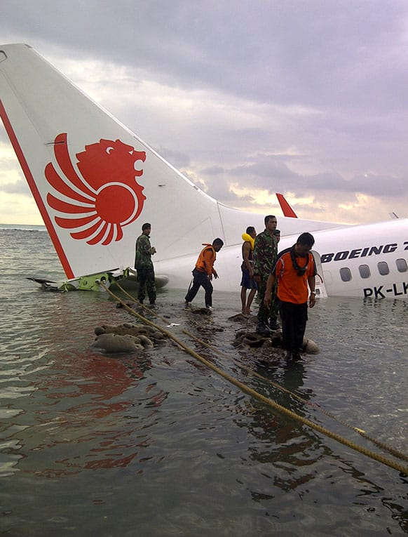 In this photo released by Indonesia`s National Rescue Team, rescuers stand near the wreckage of a crashed Lion Air plane in Bali, Indonesia.