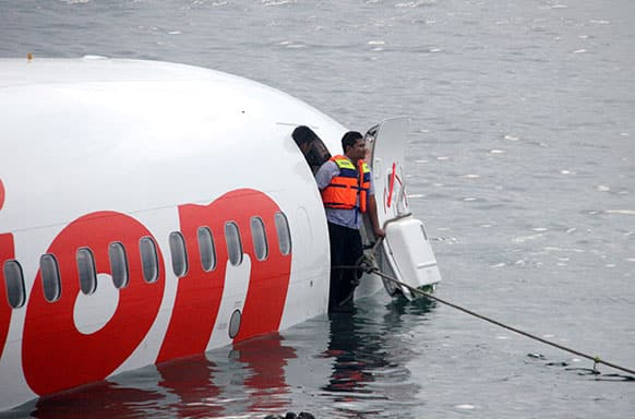 In this photo released by Indonesian Police, a rescue worker stands at the doorway of a crashed Lion Air plane on the water near the airport in Bali, Indonesia.