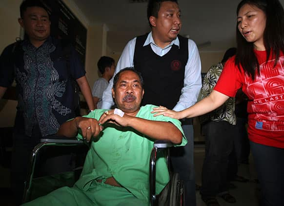 A passenger injured in a plane crash in a wheelchair is carried for medical treatment at a hospital in Jimbarn, Bali, Indonesia.