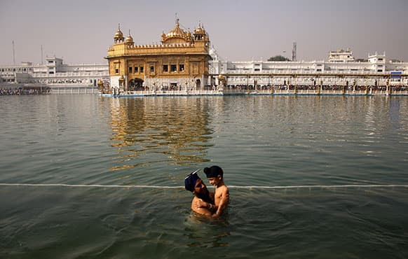 A Sikh man holds a child as they take a holy dip in the sacred pond at the Golden Temple, Sikhs holiest shrine, during Baisakhi festival in Amritsar.