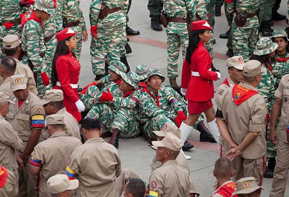 Members of the Bolivarian Militias wait for the start of a ceremony marking its` namesake day in Caracas.