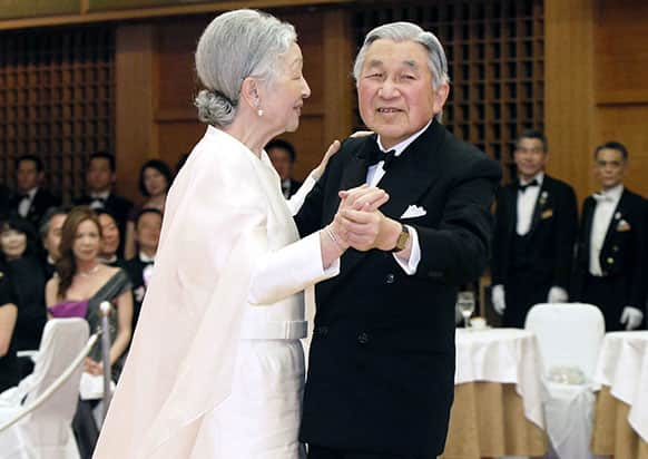 Japanese Emperor Akihito, right, and Empress Michiko dance during a dinner party for a charity in Tokyo.