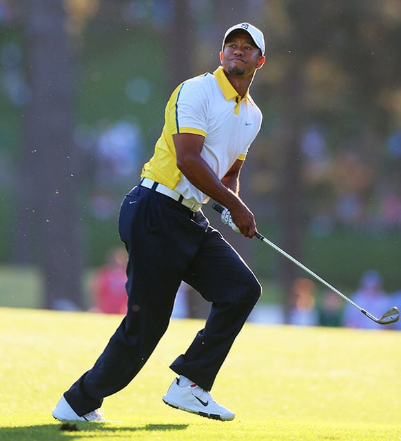 Golfer Tiger Woods reacts to his recovery shot from off the fairway over the trees to the 17th green during the second round in the Masters golf tournament in Augusta, Ga.