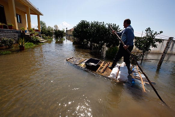 Hil Gjocaj uses a hand-made raft to drive through his yard to his house following a month-long flooding in the village of Obot, near the city of Shkoder, 120 kilometers (75 miles) northwest of capital Tirana.