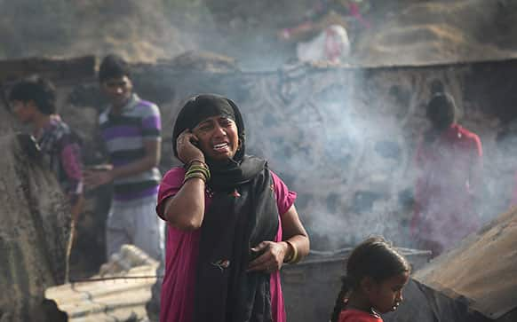 A woman cries while she talks on her mobile phone informing relatives about a fire in which her whole house was burnt in New Delhi.