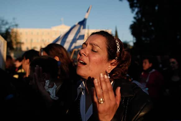 An Egyptian Coptic Christian who lives in Greece prays during a protest in central Athens.