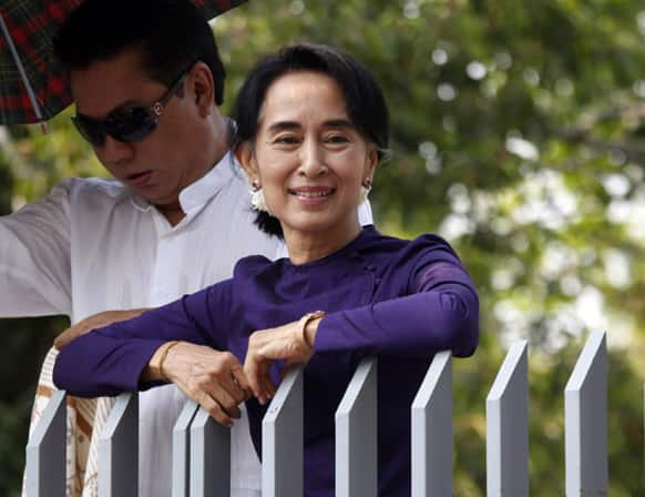 Myanmar opposition leader Aung San Suu Kyi smiles as she watches a performance of an artist troupe from the Free Funeral Service Society at the gate of her residence in Yangon.