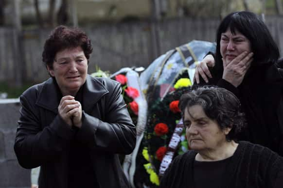 People react prior to a mass funeral of the victims of a shooting in the village of Velika Ivanca, some 50 kilometers (30 miles) southeast of Belgrade, Serbia. The village is preparing for the funerals of thirteen victims of a shooting that happened on Tuesday, April 9, 2013.