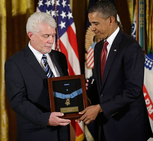 President Barack Obama stands with Ray Kapaun, left, nephew of Chaplain Capt. Emil J. Kapaun, US Army, as he awards the Medal of Honor posthumously to Chaplain Kapaun in the East Room of the White House.