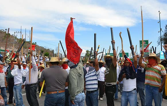 Teachers chant slogans holding up metal pipes and wooden sticks while blocking a major highway in Chilpancingo, Mexico.