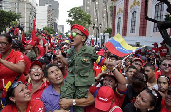 A boy dressed in military fatigues is held up by a man at a campaign rally for Venezuela`s acting president and ruling party presidential candidate Nicolas Maduro in Caracas.