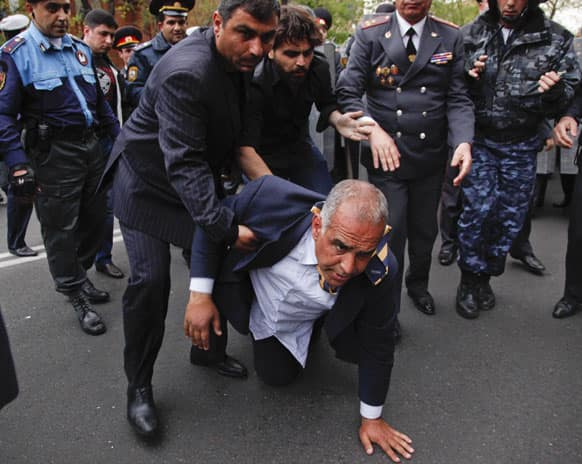 Armenian election runner-up Raffi Hovanessian is helped up after he fell during clashes between his supporters and police in Yerevan, Armenia.