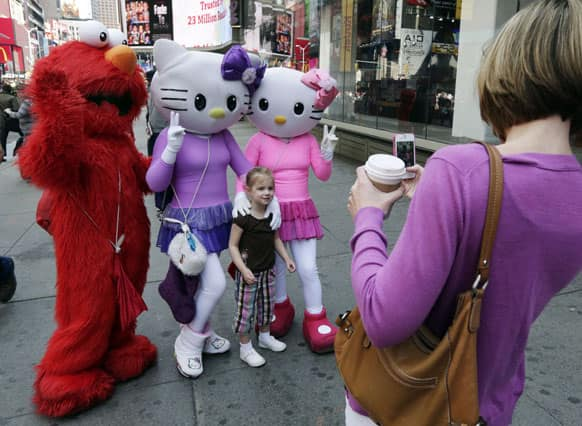 Elmo and two Hello Kitty characters pose for photos with a little girl in New York`s Times Square.