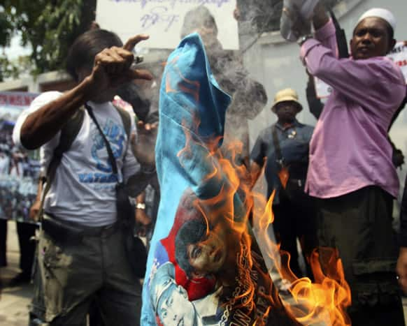 Myanmar Rohingya Muslims burn a T-shirt with an image of Myanmar opposition leader Aung San Suu Kyi, during a protest in front of Myanmar Embassy in Bangkok, Thailand.