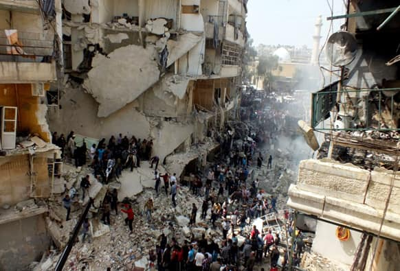 Syrian citizens searching for bodies in the rubble of damaged buildings that were attacked by Syrian forces airstrikes, in the al-Ansari neighborhood of Aleppo, Syria.