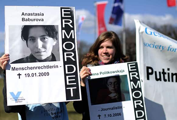 Demonstrators protest with posters of journalists Anastasia Baburova killed in 2009 & of Anna Politkovskaya killed in 2006, outside the Congress centrum in Hannover, were German chancellor Angela Merkel & Vladimir Putin are expected to meet & to deliver speeches at the Hannover Industrial Fair.