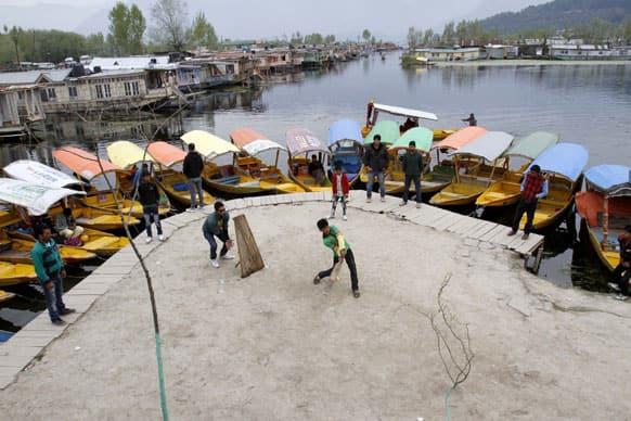Kashmiri boatmen play cricket on the banks of the Dal Lake in Srinagar.