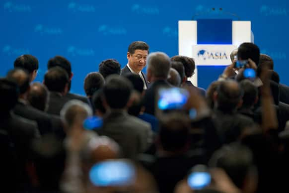 China`s President Xi Jinping, center back, walks to his seat as he arrives at the opening ceremony of the annual Boao Forum in Boao, in southern China`s Hainan province.