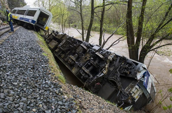 Railway workers are seen next to a derailed train carriage near Golbardo, Spain. Spanish authorities say a rockfall derailed the train, injuring 11 passengers after the first carriage partially plunged into a river just west of the northern city of Santander.