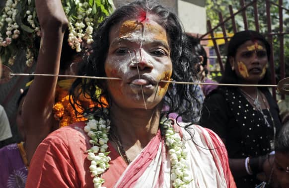 A Hindu woman devotee, cheeks pierced with a metal rod, participates in a religious procession dedicated to Goddess Mutthumariamman in Bandel, about 55 kilometers (34 miles) from Kolkata.