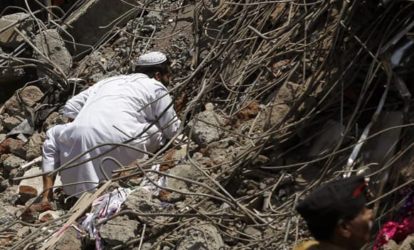 A man looks for survivors in the debris of a building that collapsed on the outskirts of Mumbai.