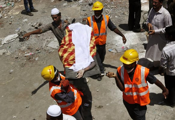 Rescue workers carry a dead body recovered from the debris of a collapsed building on the outskirts of Mumbai.