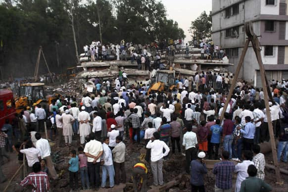 People gather as rescue workers look for trapped people after a building collapsed in Thane, Mumbai.