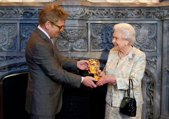 Queen Elizabeth II receives an honorary British Academy award (Bafta), at Windsor Castle, west of London, from actor and director Kenneth Branagh, in recognition of her lifetime`s support of British film and television - and for being the most