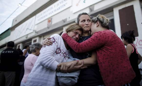People embrace outside a club where the Red Cross set up a center to help flood victims in La Plata, in Argentina`s Buenos Aires province. Buenos Aires Gov. Daniel Scioli says 49 people died in this flooded capital of Argentina's largest province as torrential rains swamped entire neighborhoods.