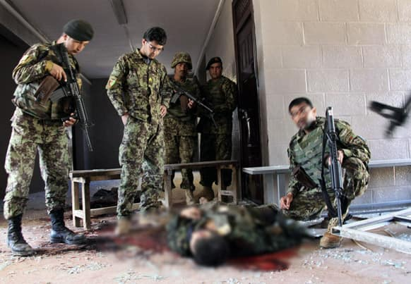 Afghan army soldiers stand around a killed Taliban, dressed as an Afghan army soldier, in the destroyed courthouse in Farah, western Afghanistan.